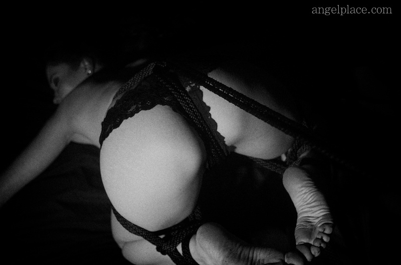 Bound and with her ass lifted - kinbaku-bi / shibari.